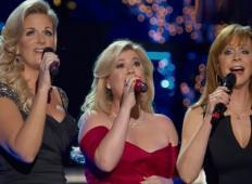 Kelly Clarkson začne peti veličastno Sveto noč. Ko se ji na odru pridružita še dve lepotici ... pravljično!