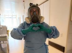Medicinska sestra dela z gas masko na glavi: Za božjo voljo, ostanite doma!